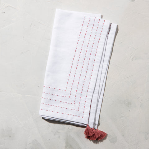white cotton napkin with terracotta embroidered stitching and terracotta tassels