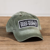 distressed olive green baseball hat with black Magnolia Seed & Supply logo patch