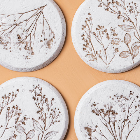 white plaster coasters with pressed floral detail