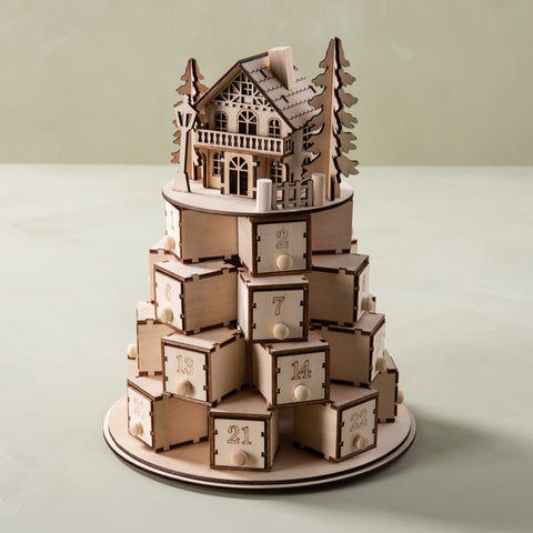 wooden tiered advent calendar with a little house on top