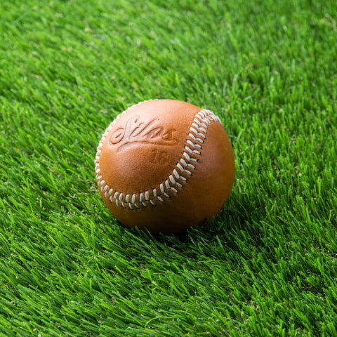 tan leather baseball with silos baseball logo and magnolia logo on the opposite side