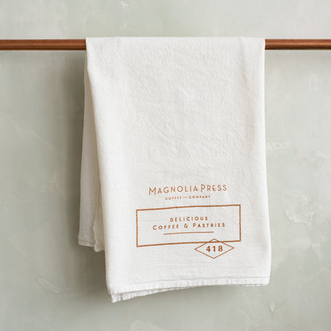 white tea towel with magnolia press logo in copper
