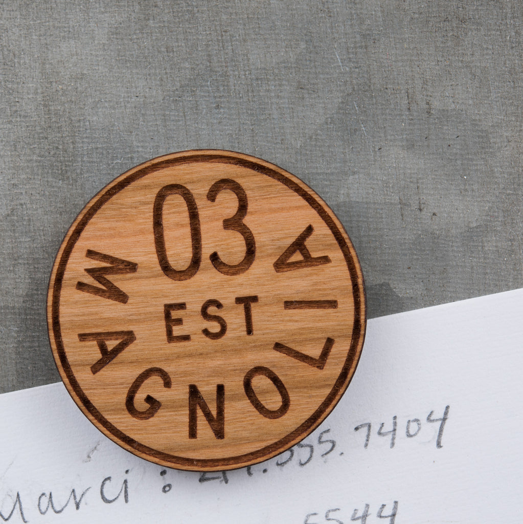 laser-engraved wood magnet with arched magnolia logo