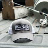 grey hat with white mesh back with black vintage magnolia logo patch