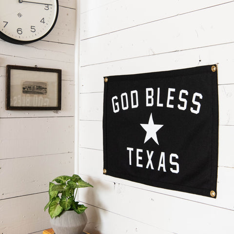 "black decorative flag that says ""god bless texas"" with a star in the center"