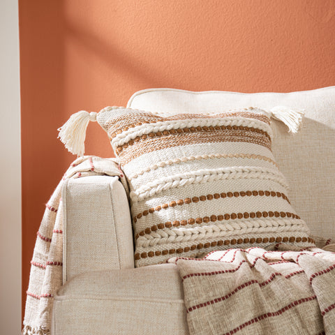 white square pillow with copper colored textured stripes and white tassels
