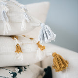 white pillow with light gray tassel detail