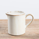white ceramic creamer with handle