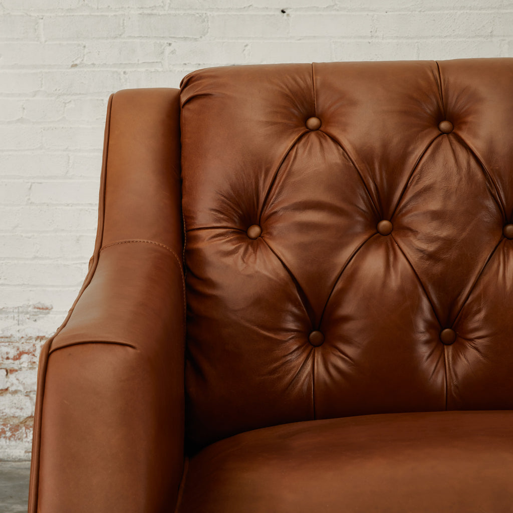 medium toned tufted leather arm chair