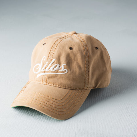 "camel colored baseball hat with ""Silos"" logo in baseball script on the front in cream"