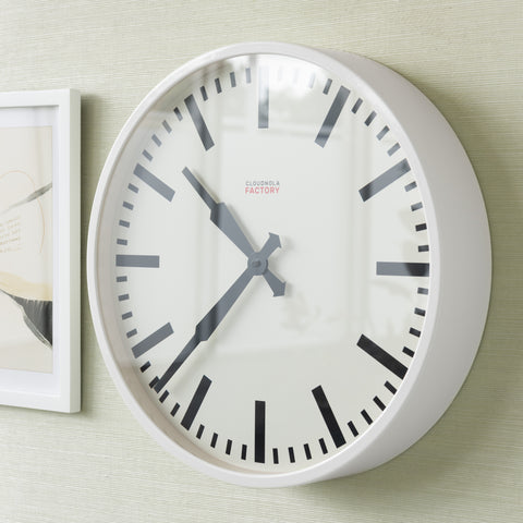 white metal wall clock with white face and black markings