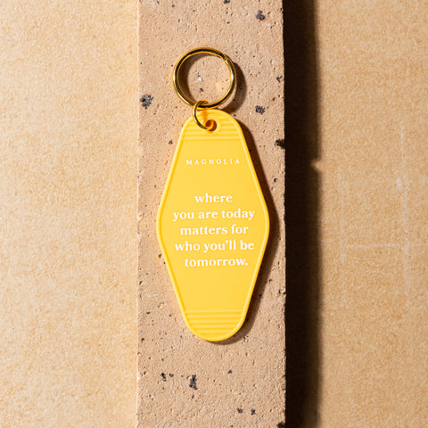 "yellow vintage hotel inspired key tag with phrase ""where you are today matters for who you'll be tomorrow"" in white"