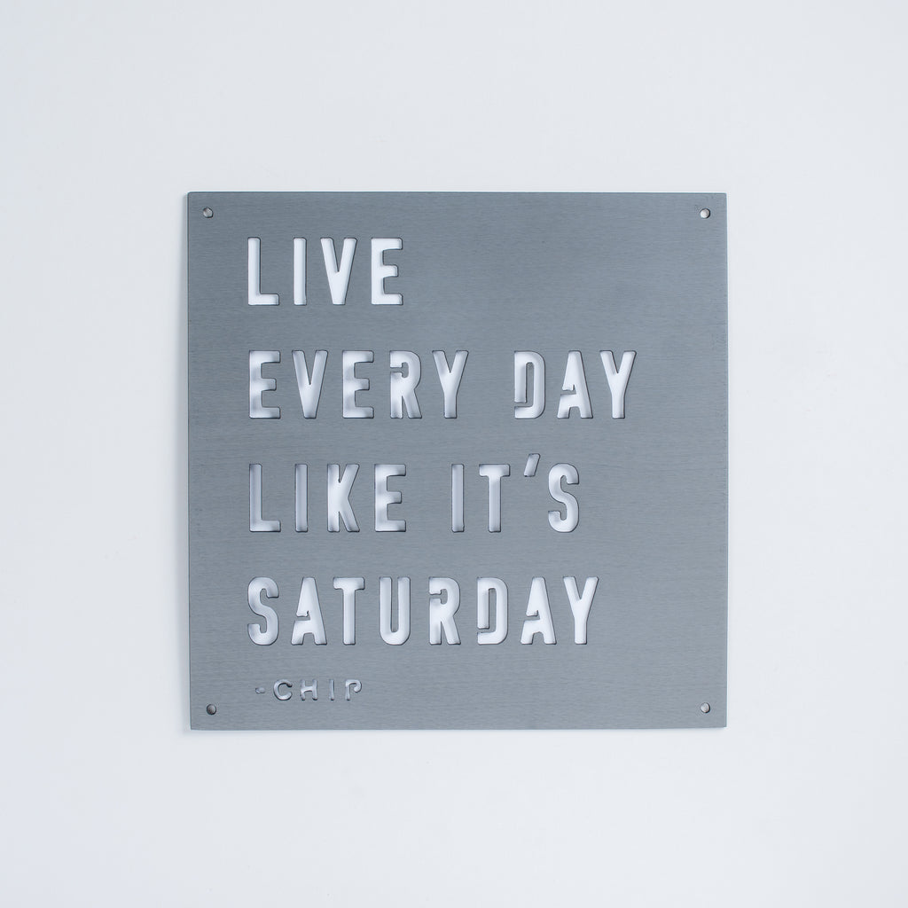 "dark grey metal quote sign that reads ""live every day like it's saturday"" - Chip"