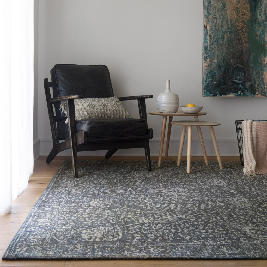 dark charcoal rug with light grey detail and traditional pattern