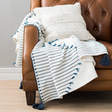 white throw with teal stripes and tassels