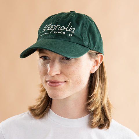 emerald green baseball hat with vintage magnolia font logo in white