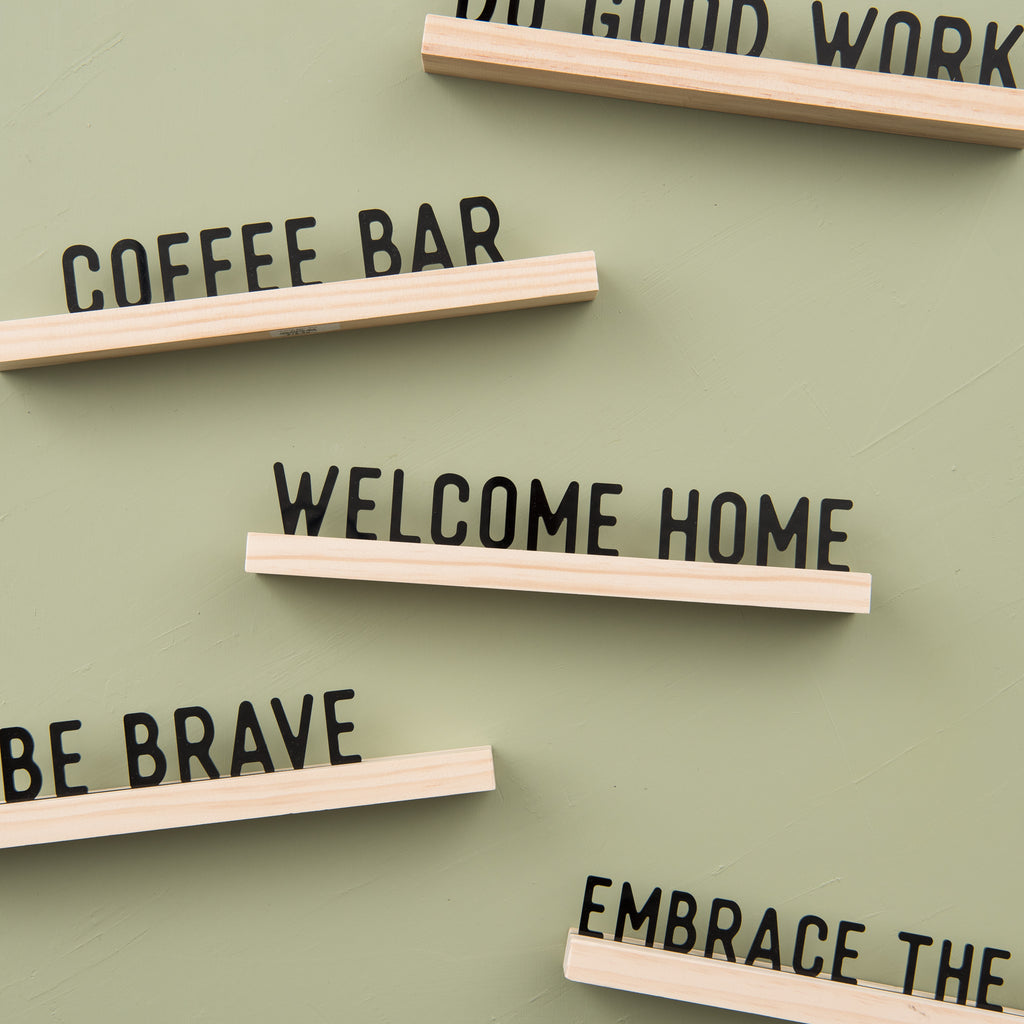"acrylic sign that reads ""welcome home"" with wooden stand"