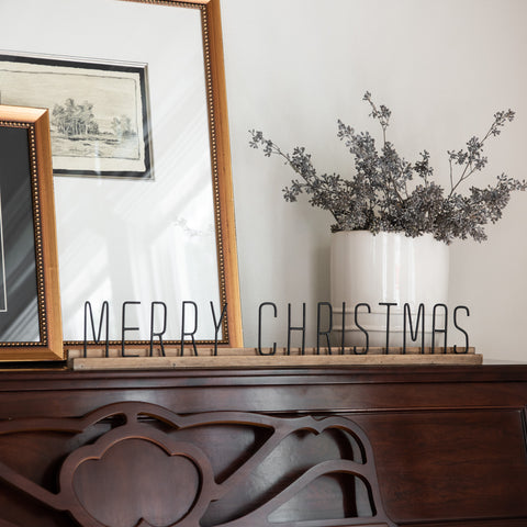 "black metal sign reading ""merry christmas"" on wooden block stand"