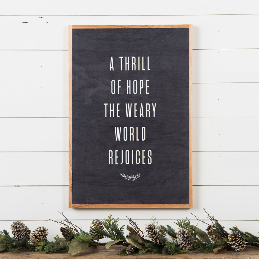 "black wooden sign with natural wood colored frame that reads ""a thrill of hope, the weary world rejoices"""