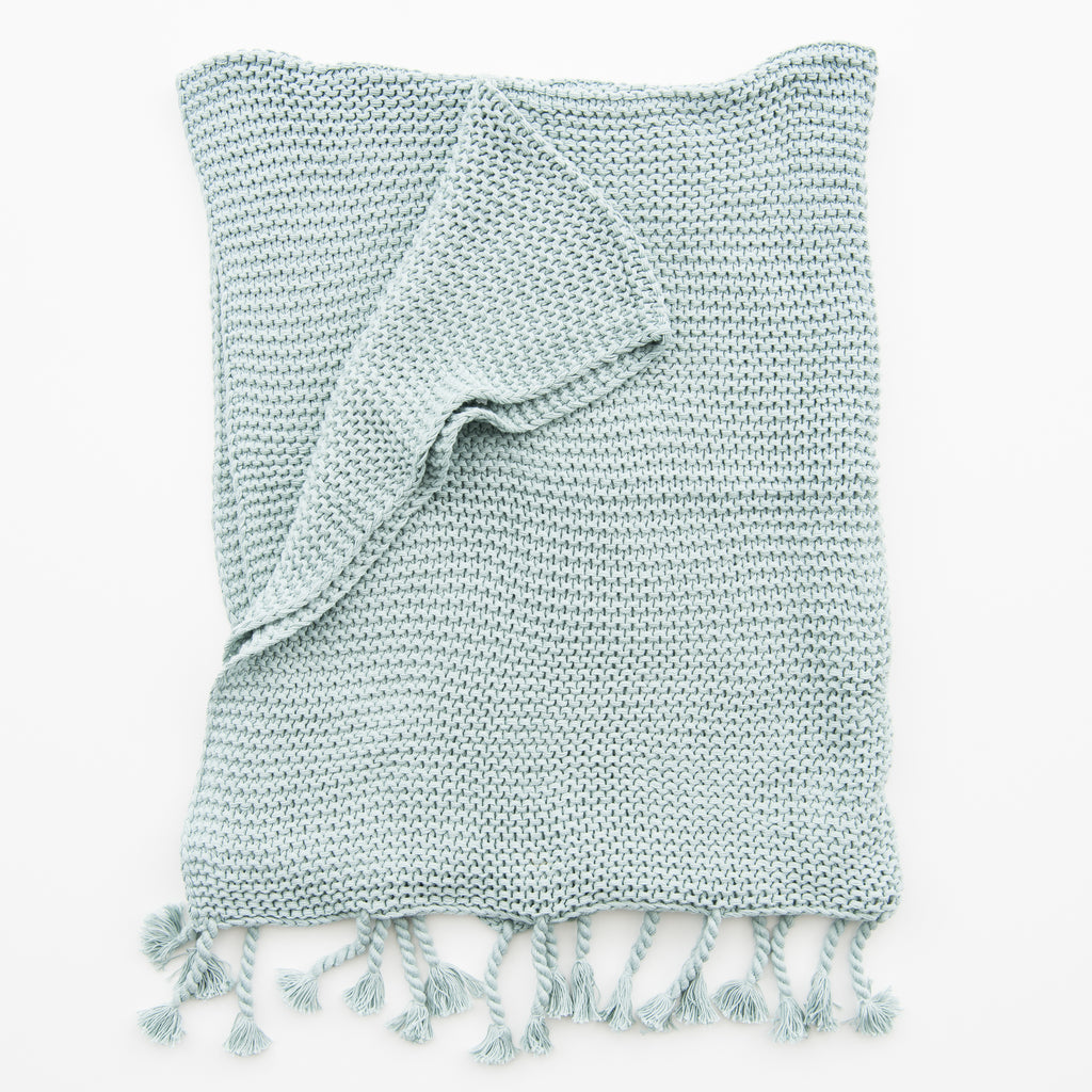 light blue knit throw with tassels.