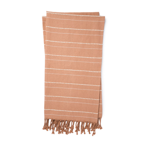 blush colored throw with white pin stripes and blush tassel fringe