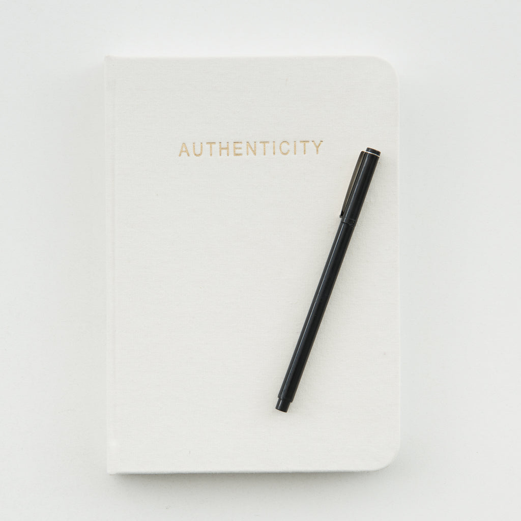 "cream journal with embossed word ""authenticity"""