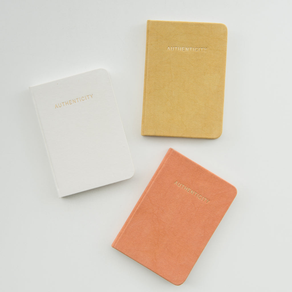 "terracotta colored journal with the word ""authenticity"" embossed in gold"