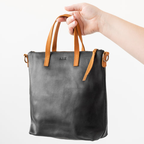 black leather tote with light brown leather handles and strap