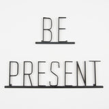 "metal quote sign that reads ""be present"""