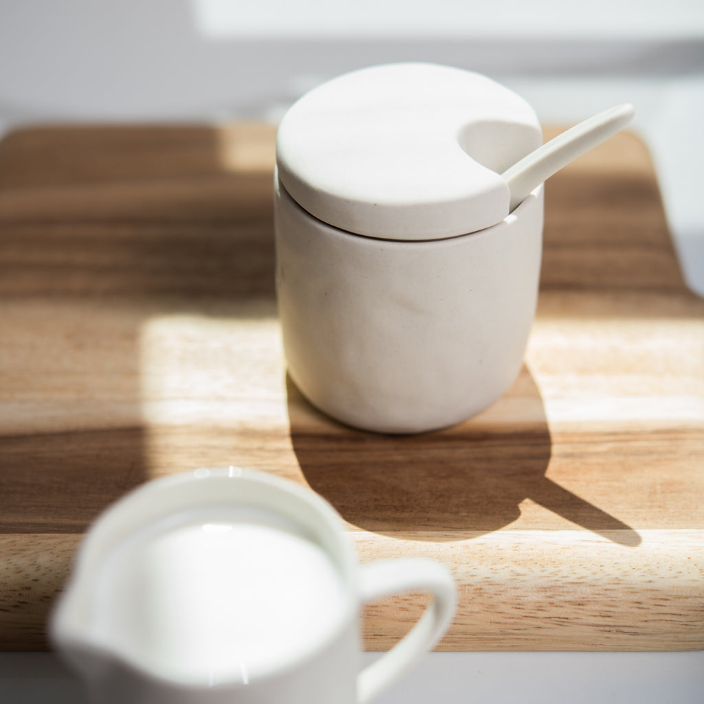 beige stoneware sugar canister with spoon