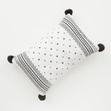 modern black and white patterned pillow with red tassels