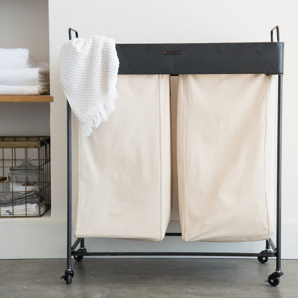black metal laundry cart on wheels with cream linen drawstring bags