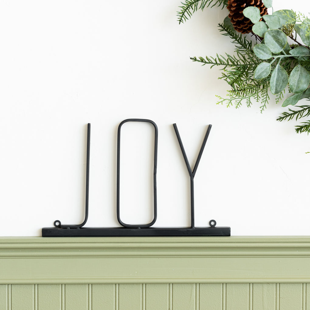 "black metal wall sign that says ""joy'"
