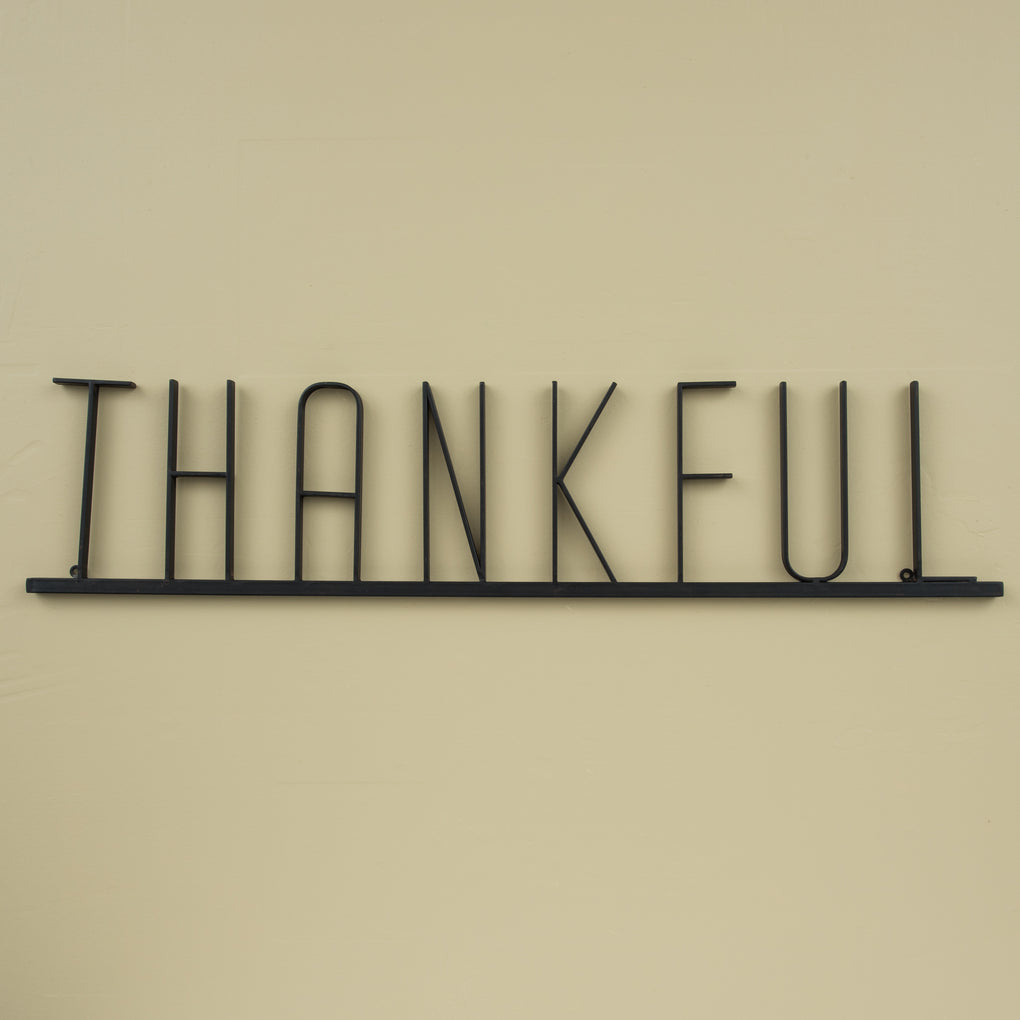 "black metal wall sign that reads ""thankful"""