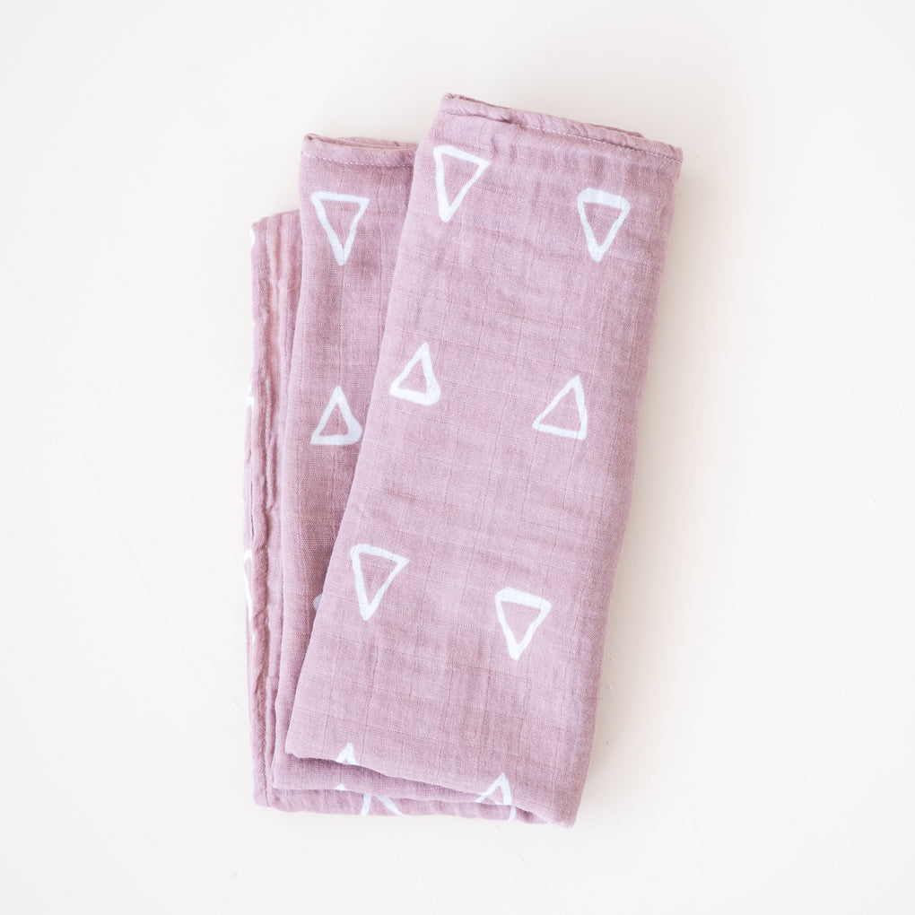 pink muslin baby blanket with white triangle pattern