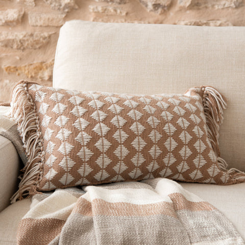 blush pink rectangular pillow with white diamond pattern and white and blush tassel fringe