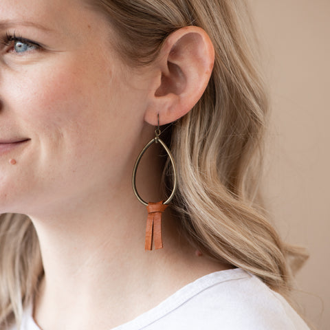 brass teardrop shaped hoop earring with brown leather tassel hanging from bottom