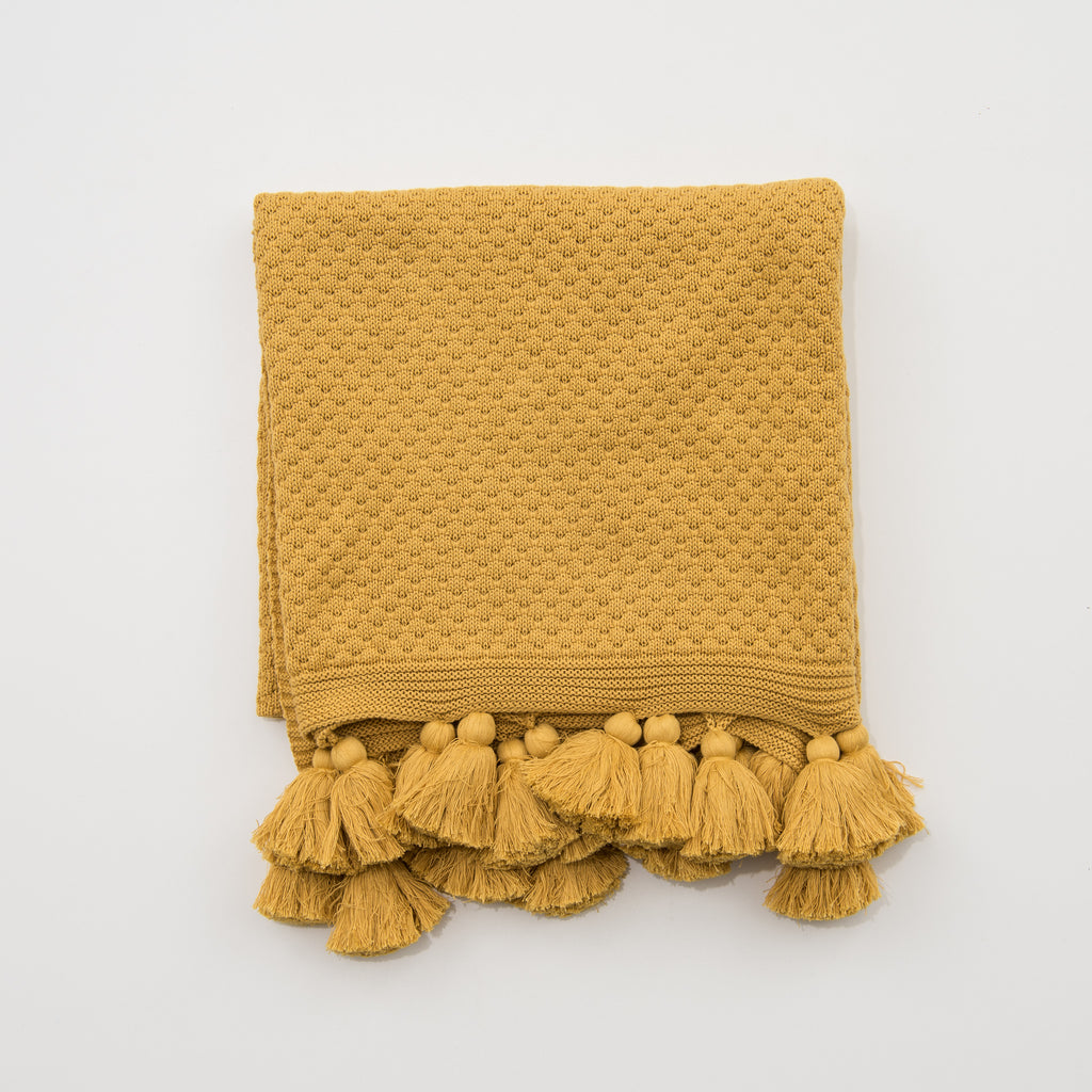 mustard colored throw with tassels