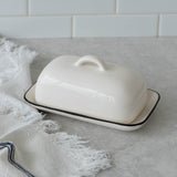 white ceramic butter dish with black rim and handled lid