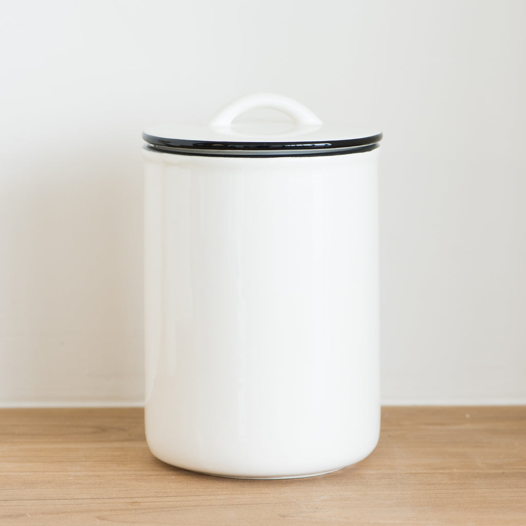 white ceramic canister with black rim and handled lid