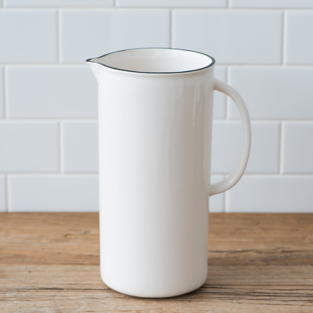 white ceramic pitcher with black rim
