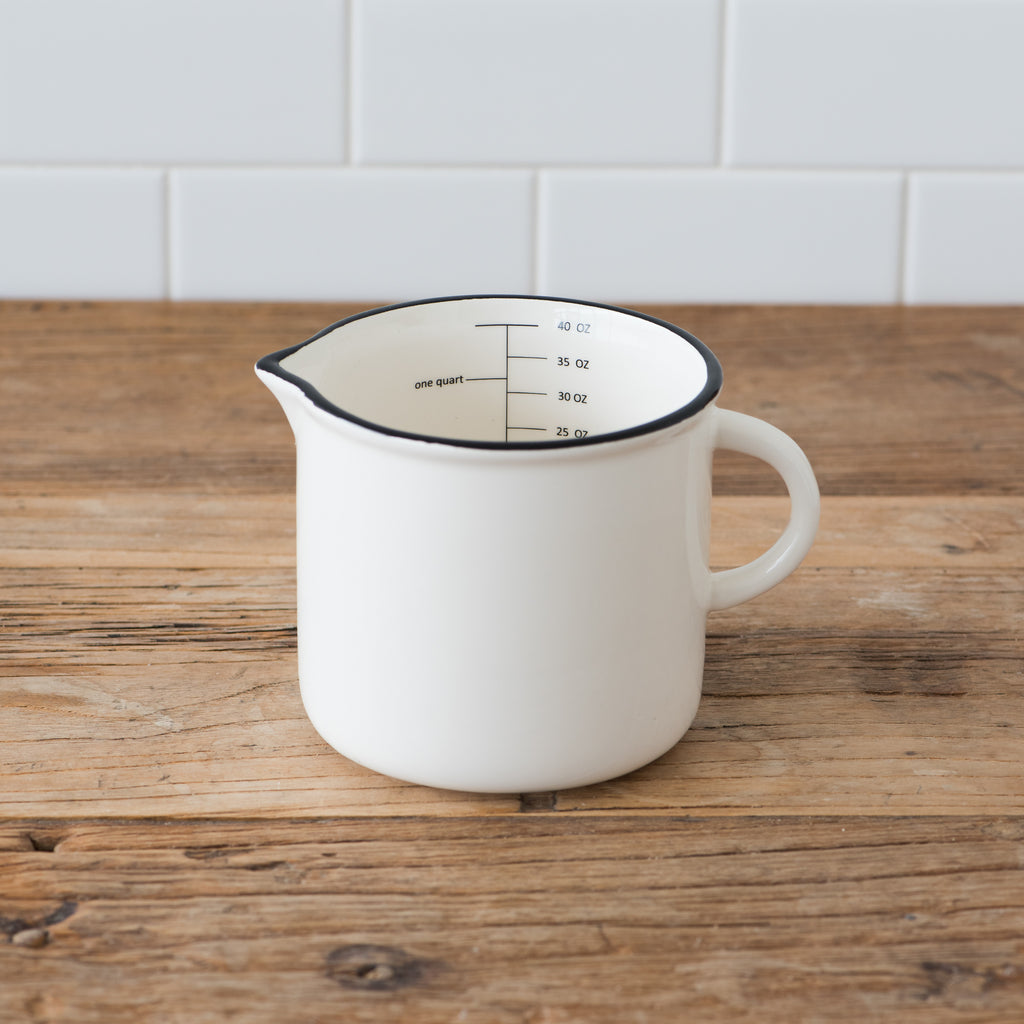 white ceramic measuring cup with handle and black rim