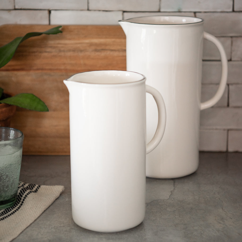 medium sized white ceramic pitcher with black rim