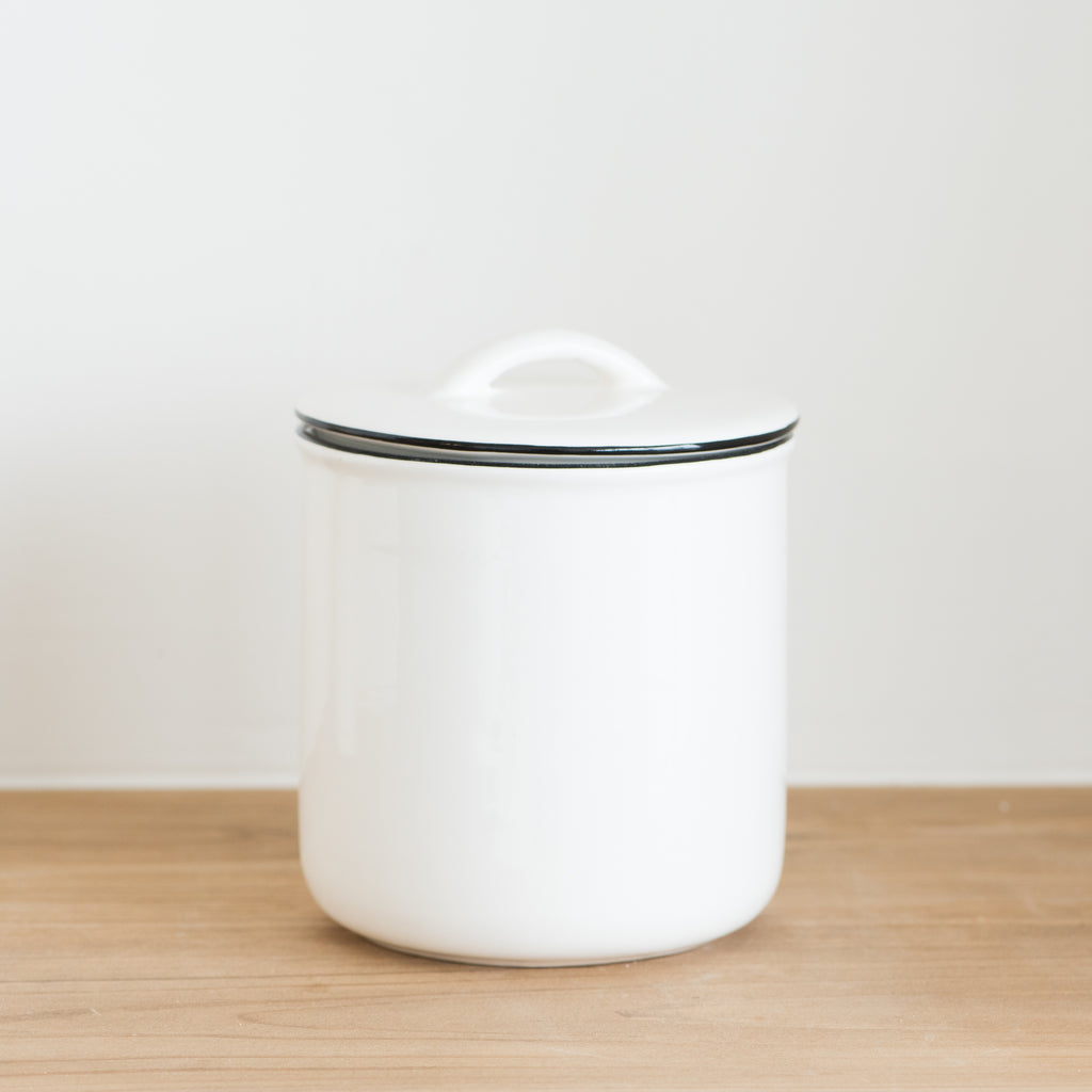 small white ceramic canister with black rim and handled lid