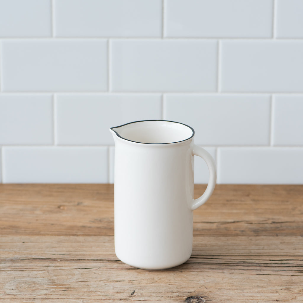small white ceramic pitcher with black rim