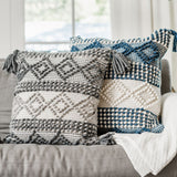 white and teal square pillow with diamonds and tassels