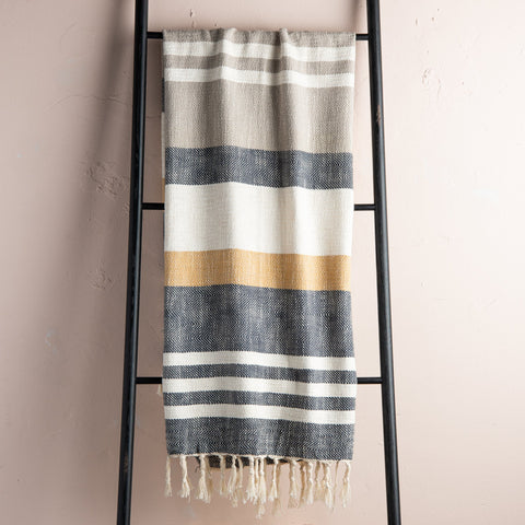 charcoal, cream, beige, and mustard striped throw blanket with beige tassel fringe