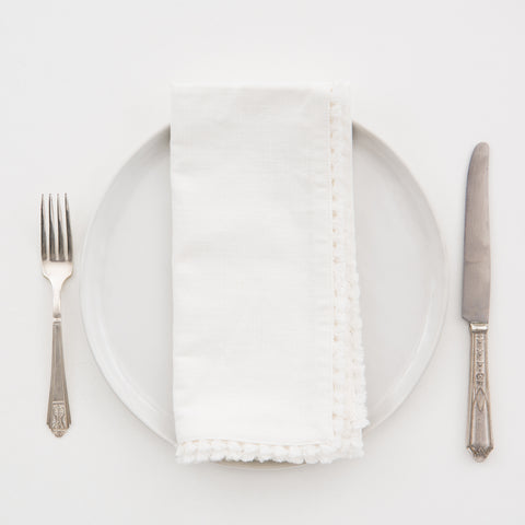 white colored cotton table napkin with embroidered edge