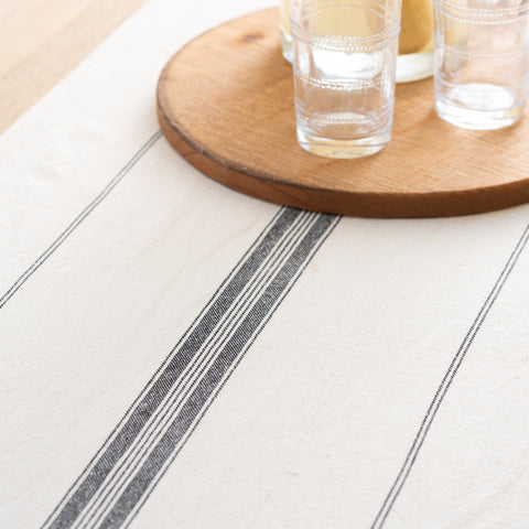 cream linen table runner with black stripe in the middle