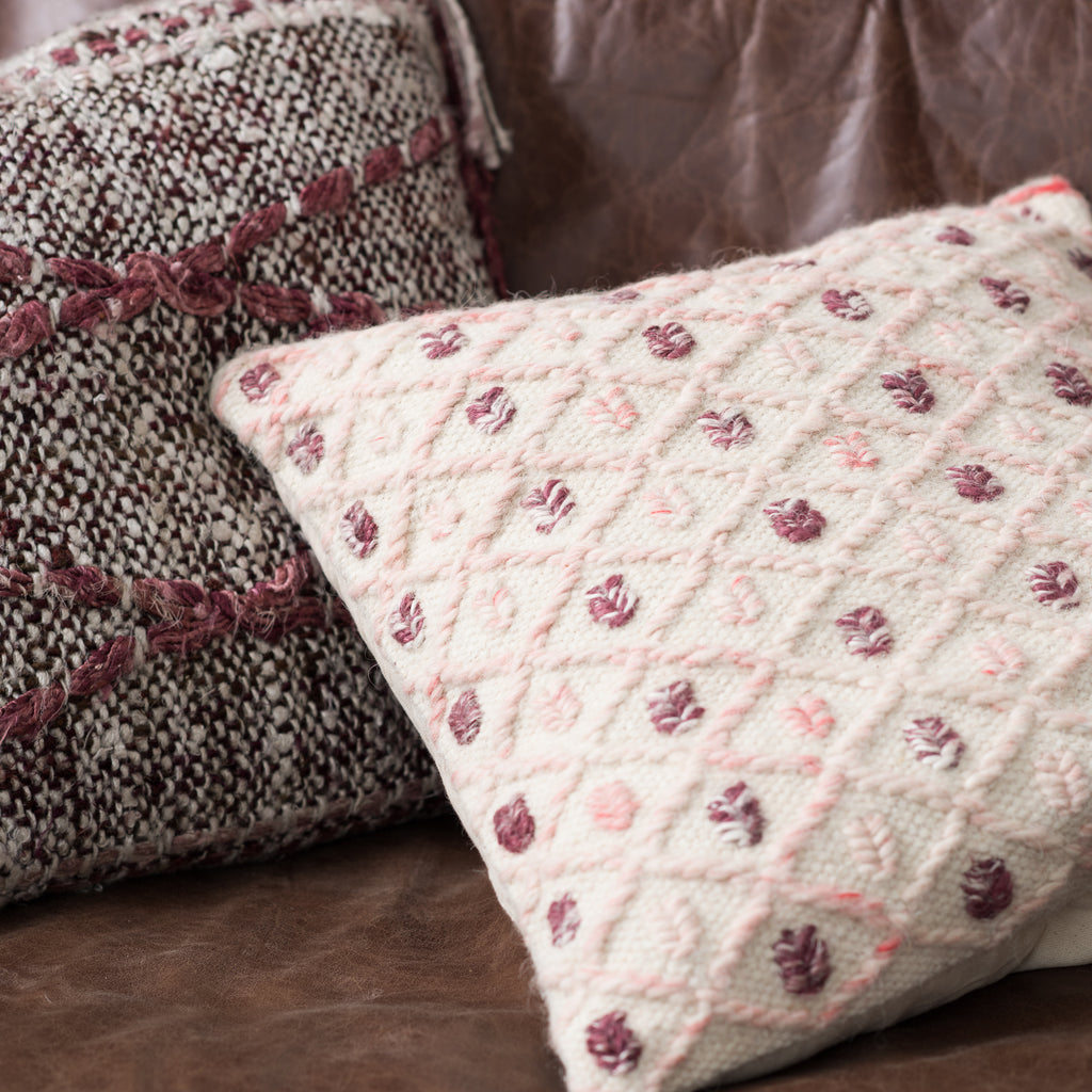 cream pillow with raised diamond pattern and pink and burgundy spots